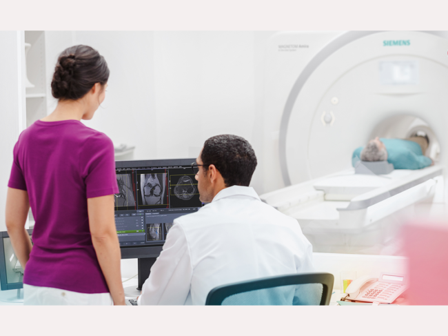 Doctor, technician look at computer while man undergoes MRI