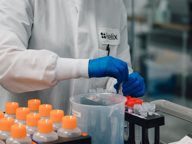 Helix employee in lab with testing tubes