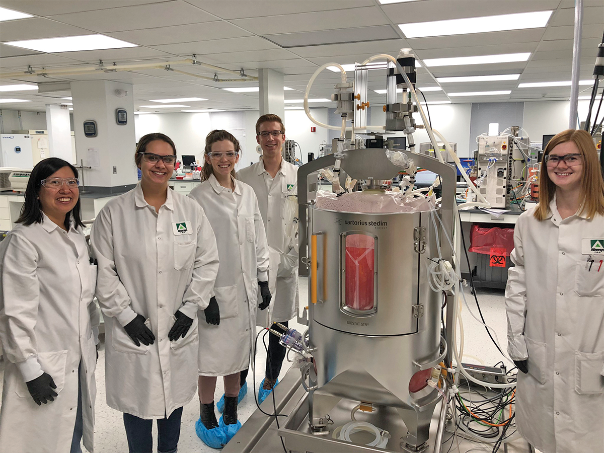 Athersys researchers standing next to bioreactor in the lab
