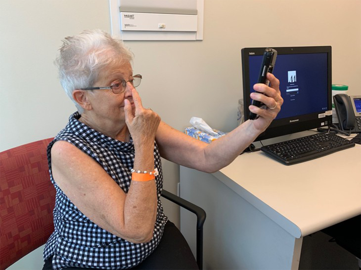 Kathryn Atkinson, an elderly patient, participating in a smartphone screening test to analyze stroke-like symptoms