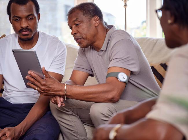 Man holding tablet, wearing armband monitor