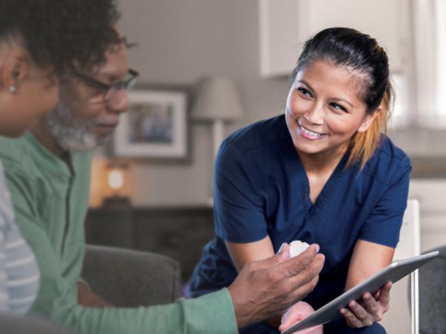 Nurse holds Ipad with elderly patients
