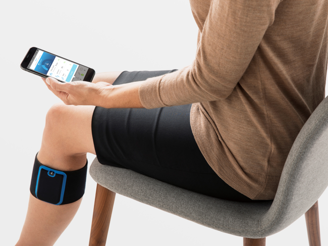 Woman sits in chair wearing Quell device below knee, using smartphone app