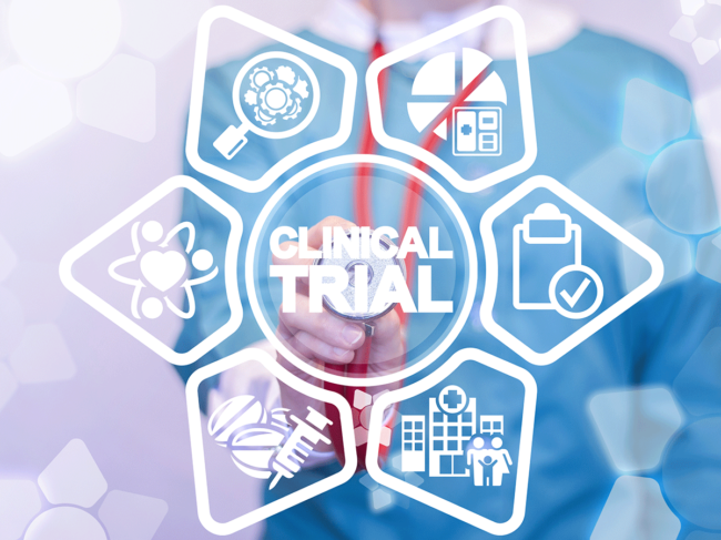Health professional pointing stethoscope at Clinical Trial words, icons