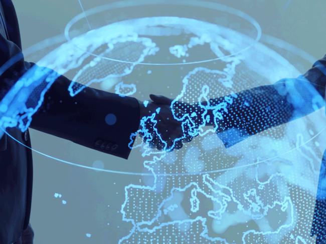 Handshake with digital globe overlay