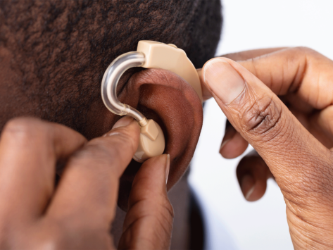 Photo of doctor inserting hearing aid in patient's ear